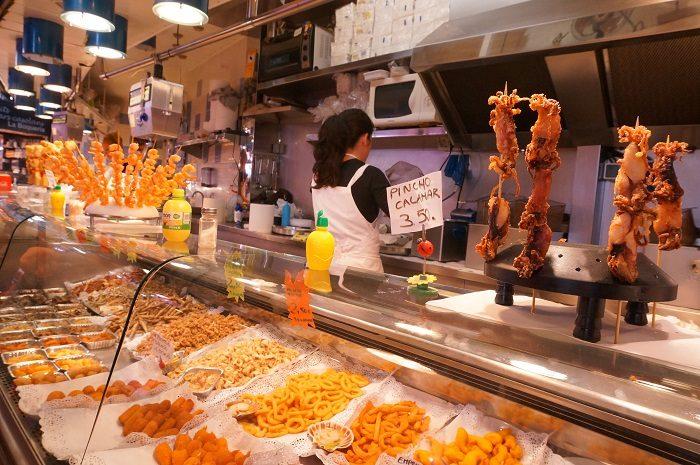 串にささったイカのフライは、食べ歩きにおすすめ。|ボケリア市場食べ歩き!おすすめの時間帯は…?