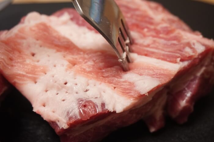 豚肩ロースの表面をフォークで刺す。