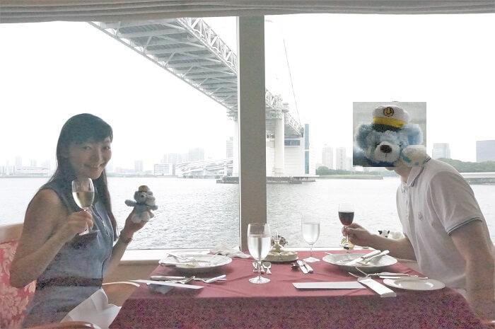 洋上で夫と記念撮影。背景にはレインボーブリッジ。